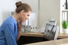 Young female receptionist talking on the phone in hospital